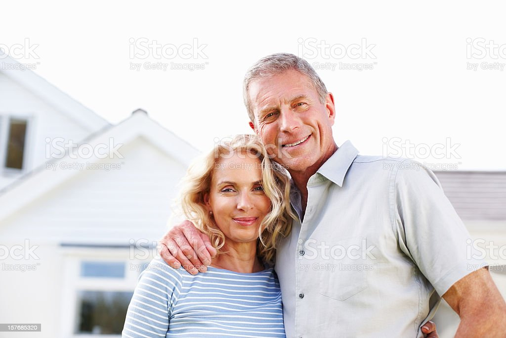 Senior man with a mature woman in front of house stock photo