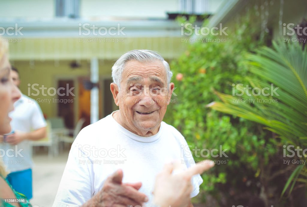 Senior man in his 90's looks at the camera with a laugh and smile in...