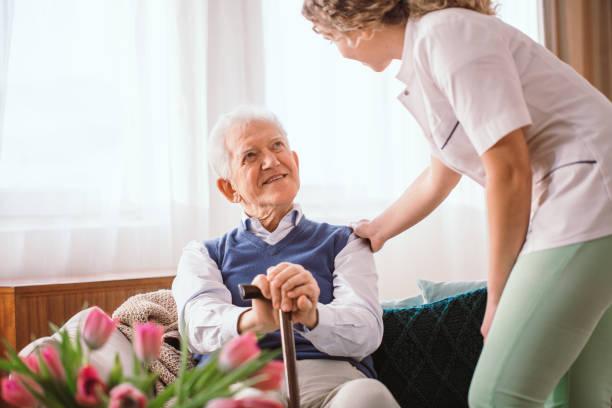 Seniorenmann mit einem Gehstock, der von Krankenschwester im Hospiz getröstet wird – Foto
