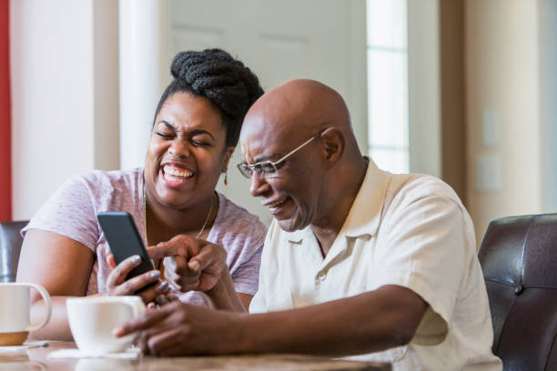 Senior man with adult daughter using smart phone stock photo