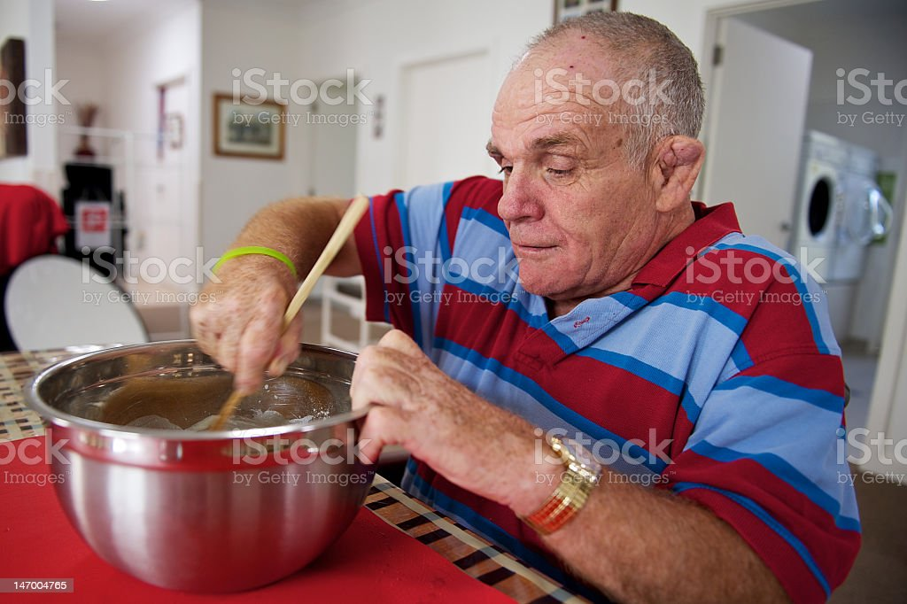 Senior man with an intellectual disabilityinvolved in meal preparation. stock photo