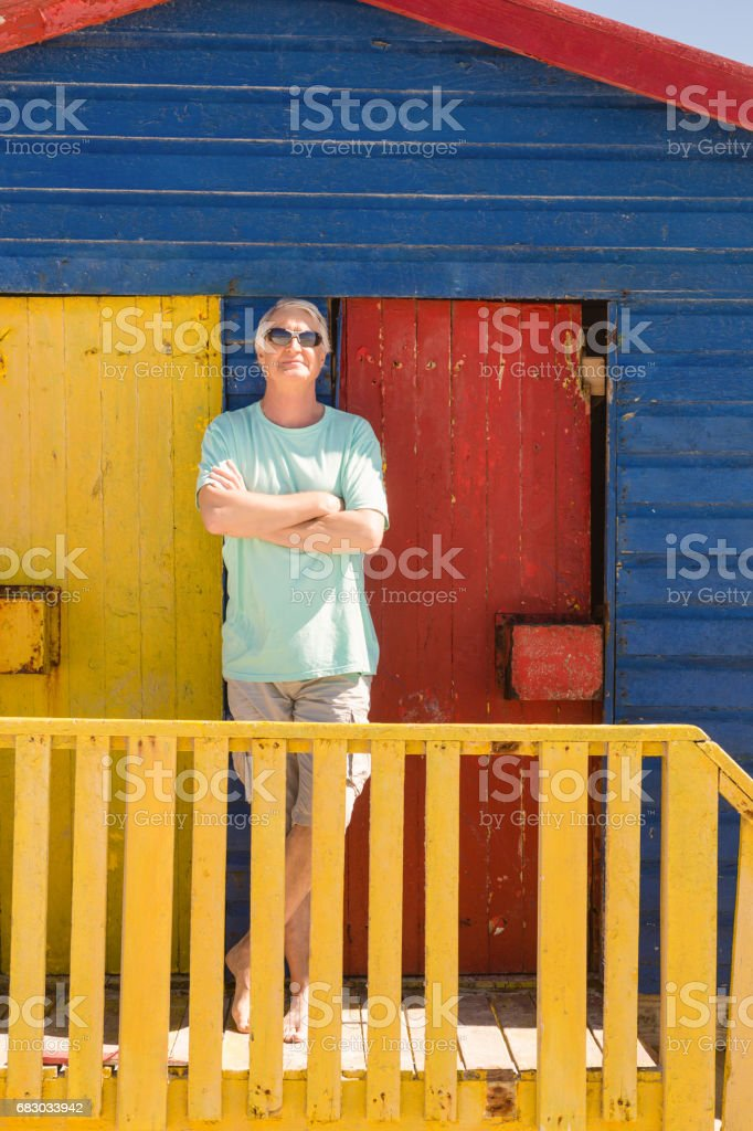 Senior man with arms crossed standing by railing of beach hut foto de stock royalty-free