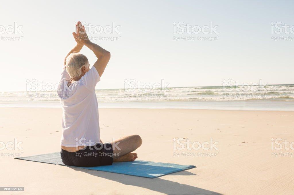 老人用雙臂上舉冥想在海灘 免版稅 stock photo