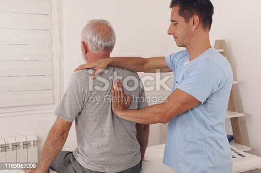 885281276istockphoto Senior man with back pain. Spine physical therapist and paient. chiropractic pain relief therapy. Age related backache 1183067005