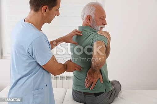 885281276 istock photo Senior man with back pain. Spine physical therapist and paient. chiropractic pain relief therapy. Age related backache 1183067061