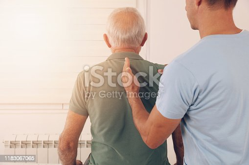885281276istockphoto Senior man with back pain. Spine physical therapist and paient. chiropractic pain relief therapy. Age related backache 1183067065