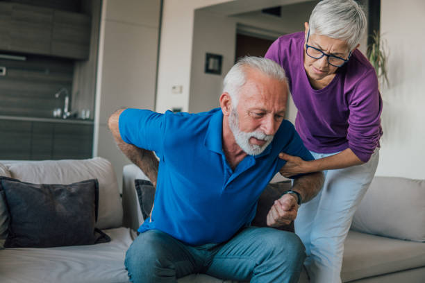 Senior man with backache Mature woman helping the man with backache back pain stock pictures, royalty-free photos & images