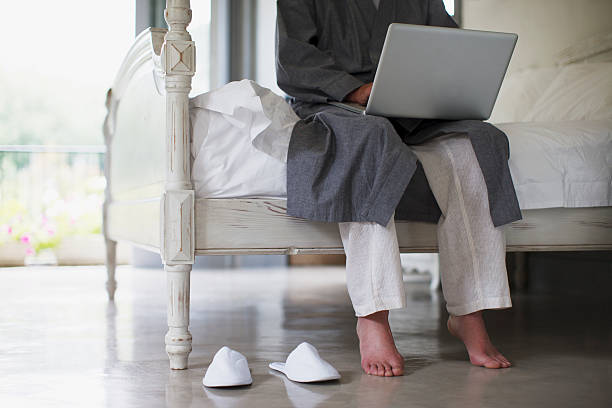 senior man with bare feet sitting on edge of bed using laptop - old man feet stock photos and pictures