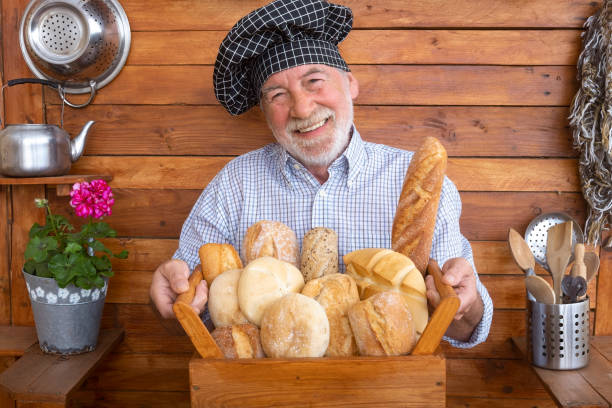 een hogere mens met baard en chef-kokglb houdt een mand met vers brood dat met verschillende bloemen wordt gemaakt. rustieke achtergrond in gerecycleerd hout - gelukkig pensioneringsconcept - oldman chef's cap hat stockfoto's en -beelden