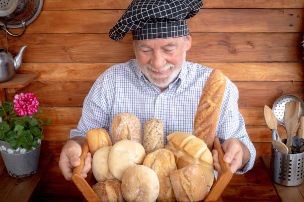 een hogere mens met baard en chef'sglb houdt een houten mand met vers brood dat met verschillende bloem wordt gemaakt. rustieke achtergrond in gerecycleerd hout - oldman chef's cap hat stockfoto's en -beelden