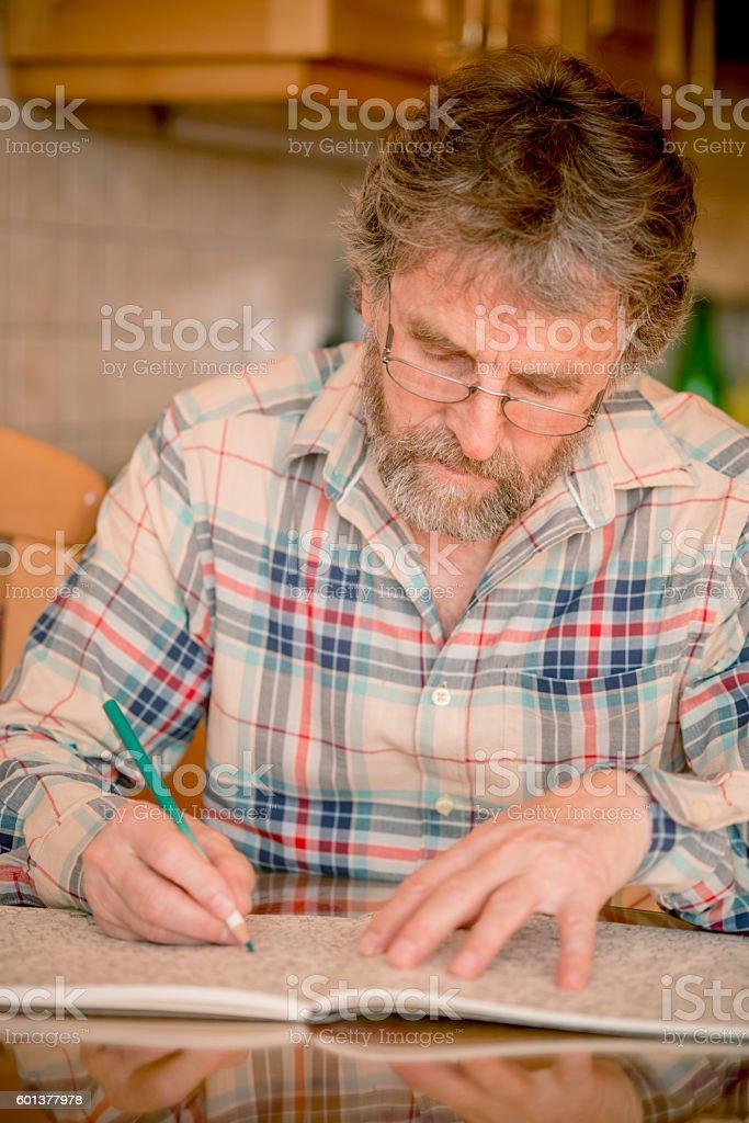 Senior Man with Beard Coloring Book at Home, Slovenia,  Europe stock photo