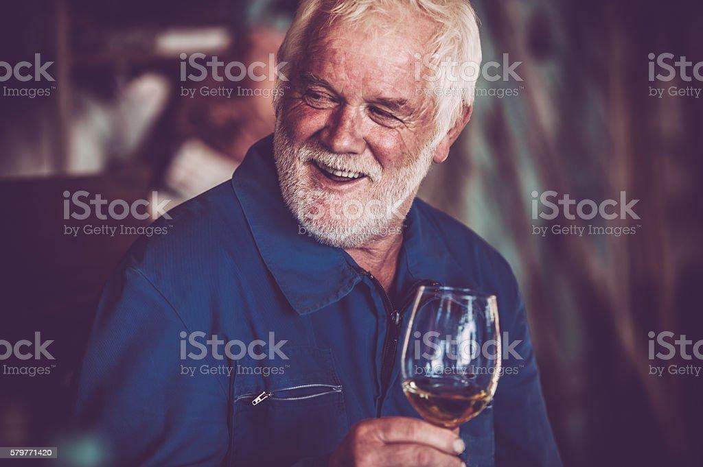 Senior Man with Beard Drinking Glass of White Wine stock photo