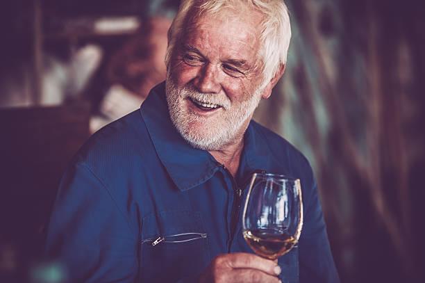 Alter Mann mit Bart trinkt ein Glas Weißwein – Foto