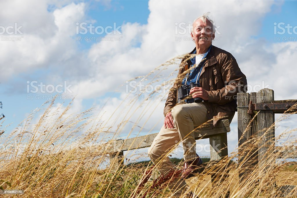 Senior Man With Binoculars Sitting On Wooden Gate stock photo
