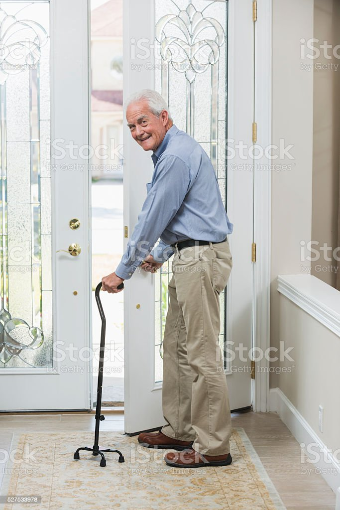 Senior man with cane coming home, opening front door stock photo