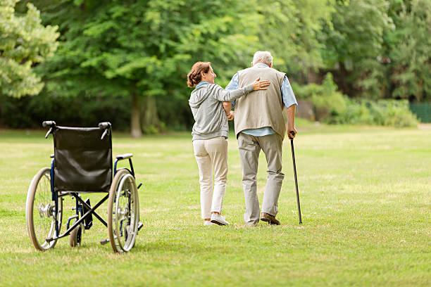 senior man with caregiver at the park - 高齢者介護 ストックフォトと画像