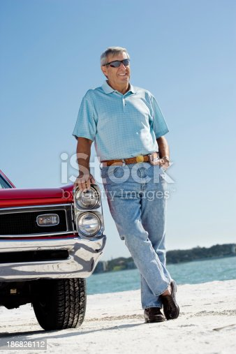 530979971istockphoto Senior man with classic convertible car 186826112