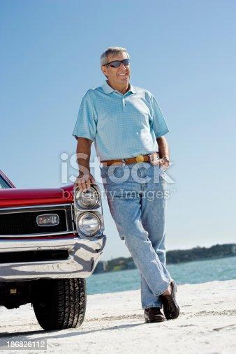 istock Senior man with classic convertible car 186826112
