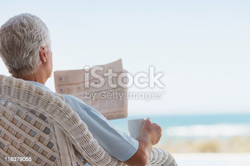 116379055 istock photo Senior man with coffee and newspaper on beach patio 116379055