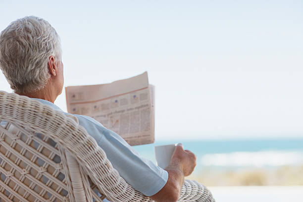 senior man with coffee and newspaper on beach patio - newspaper beach stockfoto's en -beelden