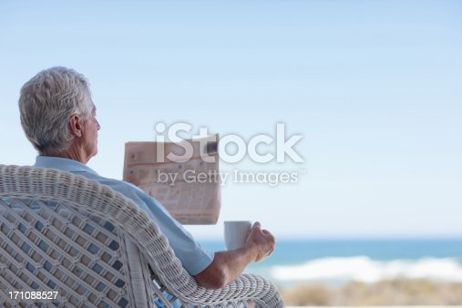 116379055 istock photo Senior man with coffee and newspaper on beach patio 171088527