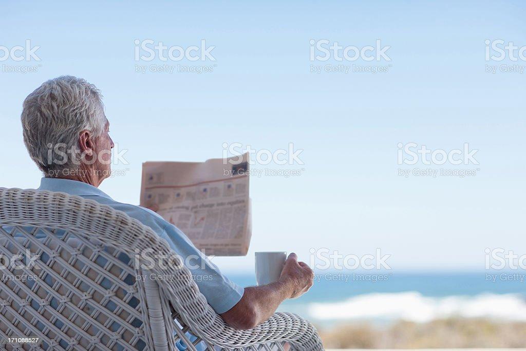 Senior man with coffee and newspaper on beach patio stock photo