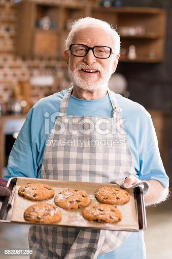 istock Senior man with cookies 683981286