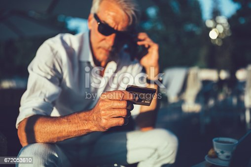 502723248 istock photo Senior man with credit card calling the bank 672053610