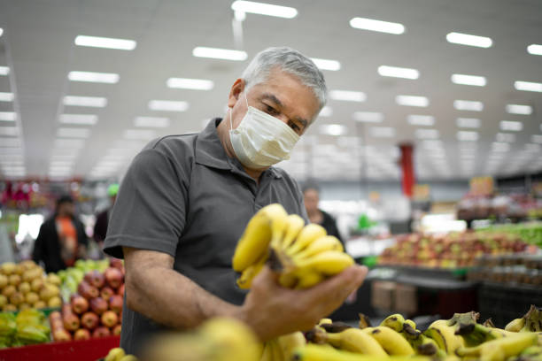 Senior man with disposable medical mask shopping in supermarket stock photo
