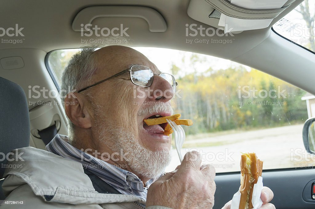 senior man with expressive face eating  fast foods stock photo