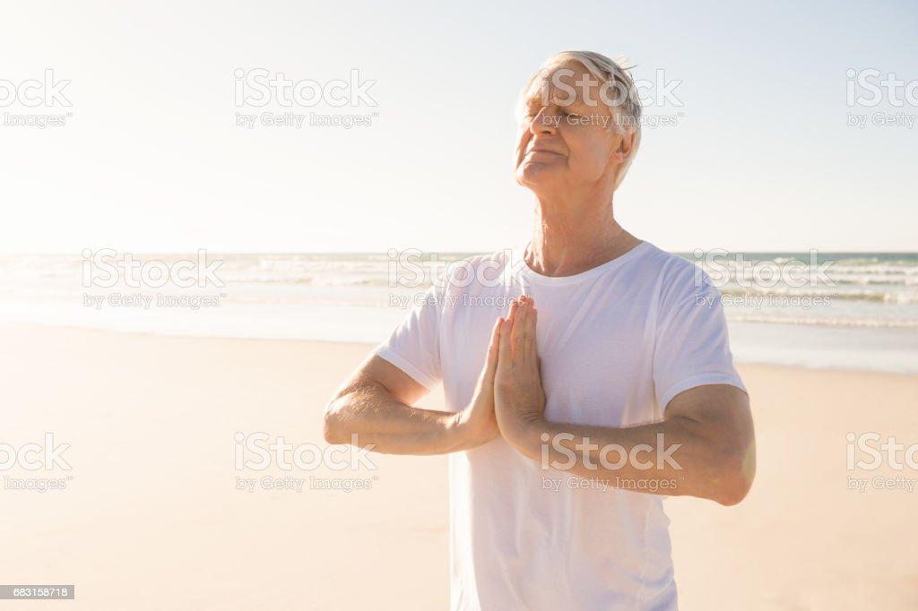 老人在祈禱位置在海灘閉著眼睛 免版稅 stock photo
