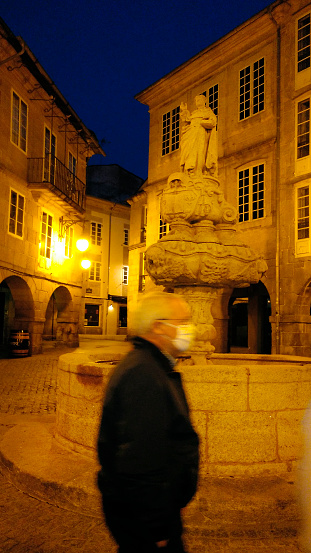 Senior man with face mask, old  town square in Lugo, Galicia, Spain. Pandemic.