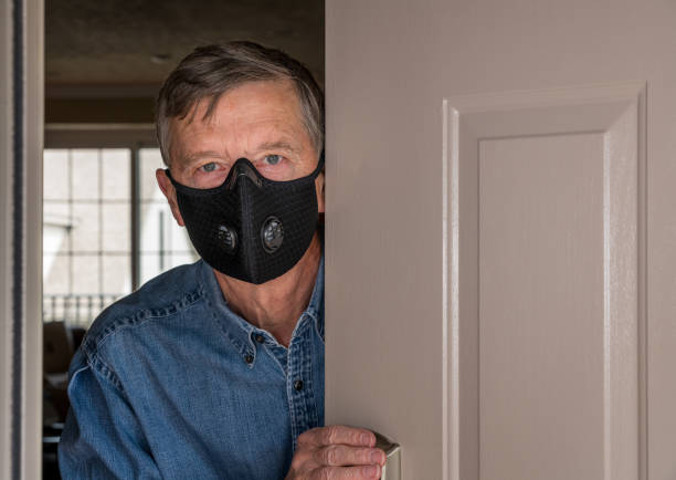 Senior man with face mask peering through front door for visitors during quarantine stock photo