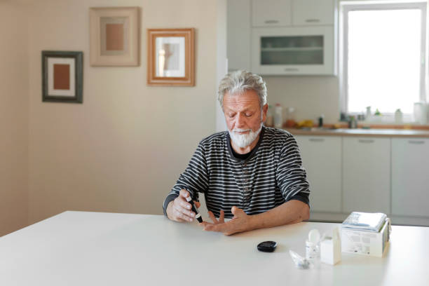 Senior man with glucometer Senior man with glucometer checking blood sugar level at home. Elderly man testing for high blood sugar. Man holding device for measuring blood sugar. medicine, age, diabetes, healthcare and old people concept lancet arch stock pictures, royalty-free photos & images