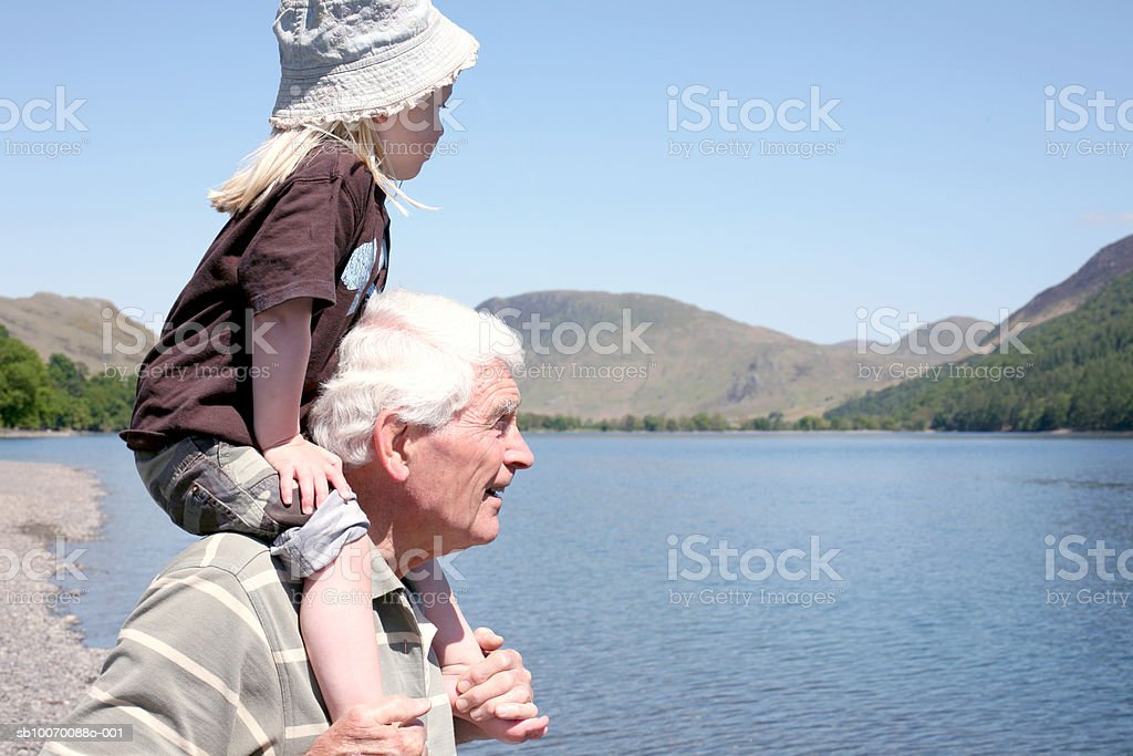 Senior man with granddaughter (2-3) on shoulders by lake royalty-free stock photo