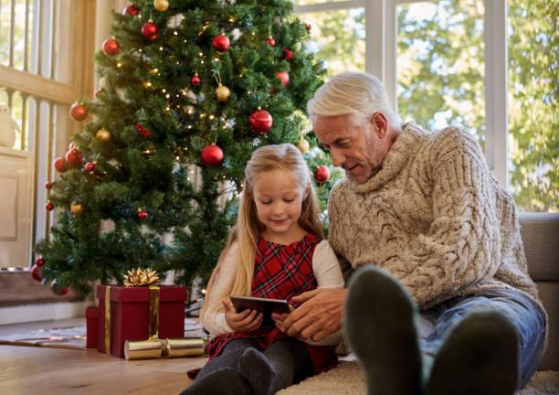 ältere mann mit enkelin mit digital-tablette in der weihnachtszeit - alte weihnachtsbäume stock-fotos und bilder