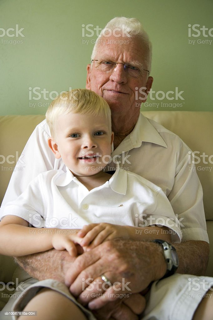 Senior man with grandson (4-5) on lap, portrait royalty free stockfoto