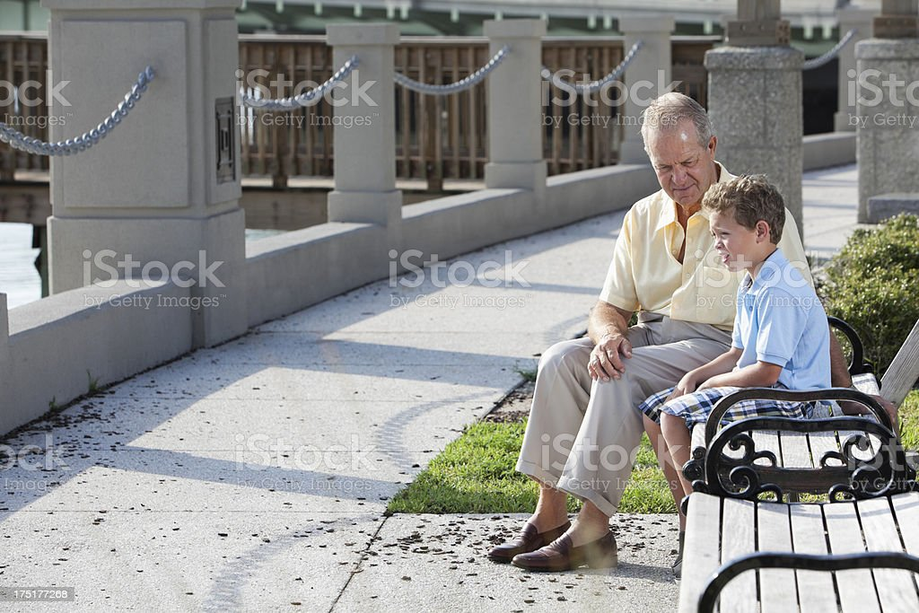Senior man with grandson on park bench stock photo