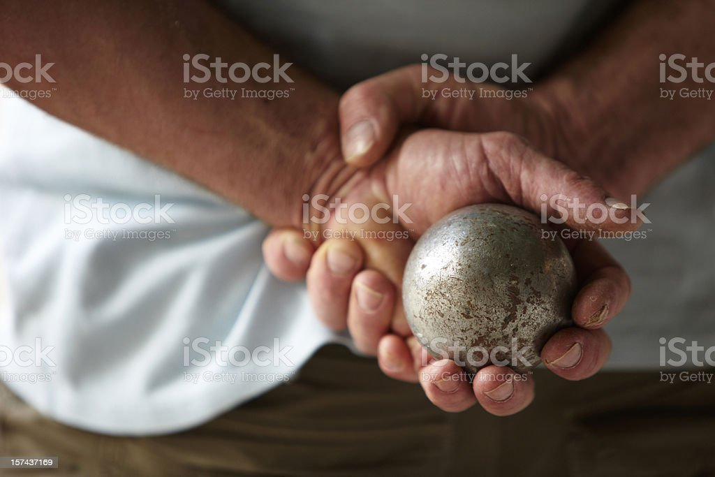 Senior man with hands behind his back holding a metal ball stock photo