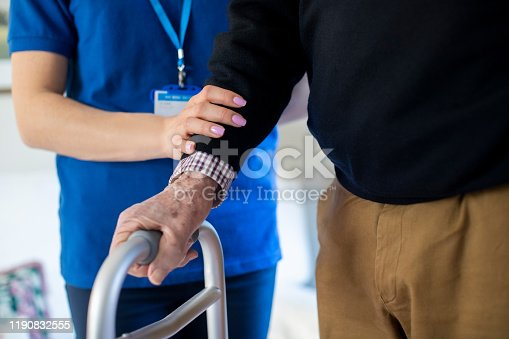 istock Senior Man With Hands On Walking Frame With Care Worker 1190832555