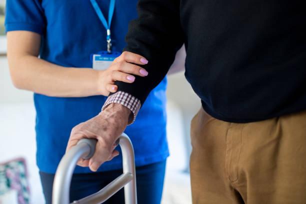 senior man with hands on walking frame with care worker - alterungsprozess stock-fotos und bilder
