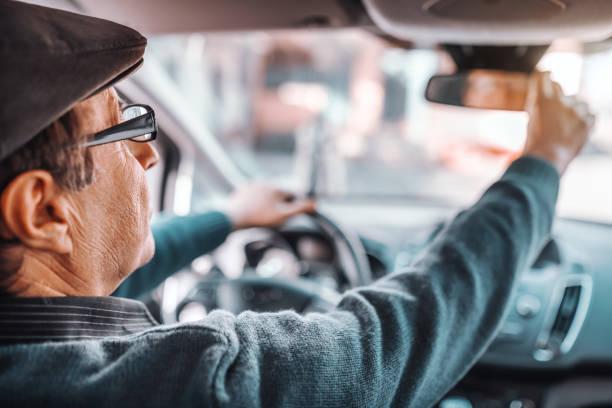 seniorenmann mit hut und brille, die den rückspiegel im sitzen in seinem auto anpasst. andere hand am lenkrad. foto vom rücksitz. - berufsfahrer stock-fotos und bilder