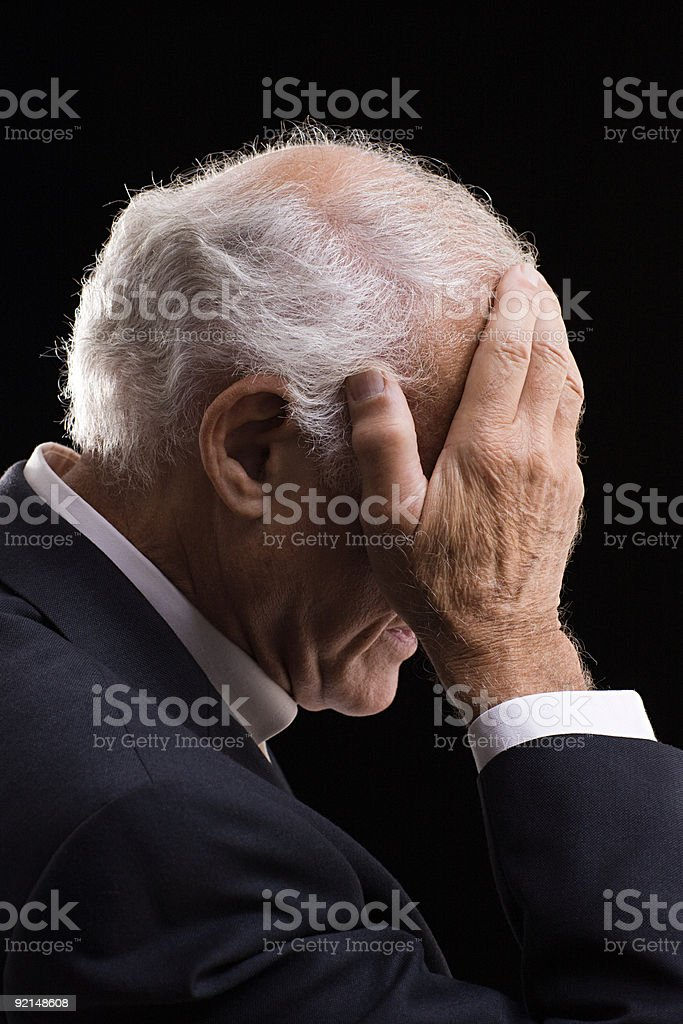 Senior man with head in hands stock photo