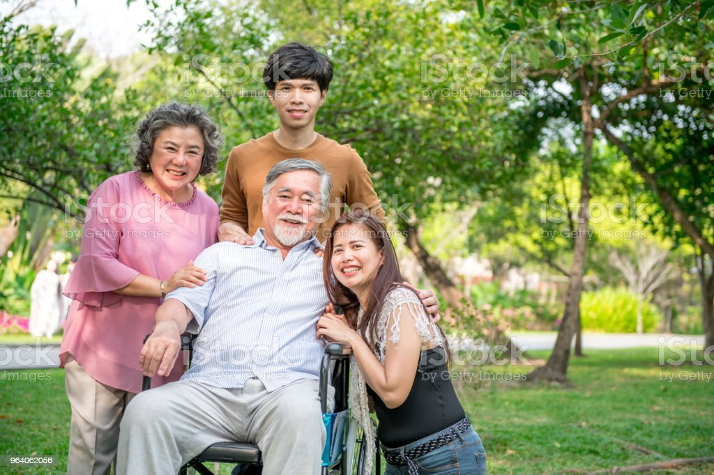 Senior man with his family in park. Chinese old man in wheel chair and his senior chinese wife, grand son and daughter relaxing together, talking to each other. Family insurance concept. - Royalty-free Adult Stock Photo