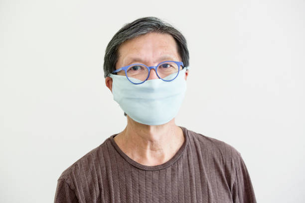 COVID-19 Senior Man with Homemade Face Mask for Social Distancing stock photo