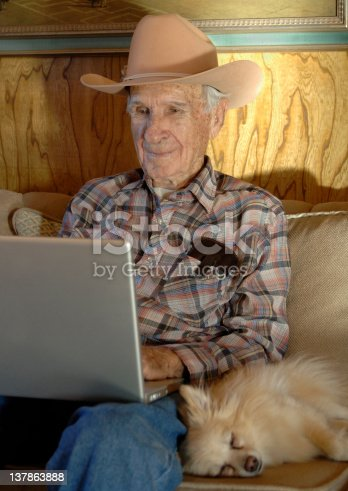 Senior Man wearing a cowboy hat works with a Laptop Computer