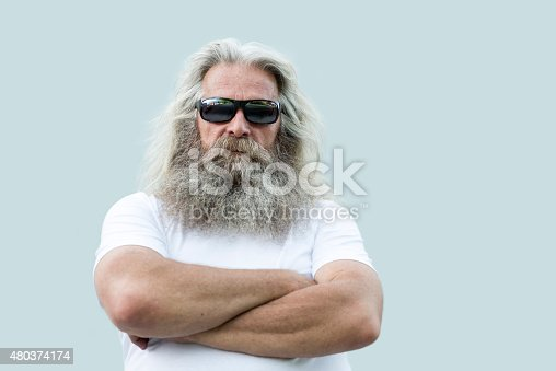 A portrait of a senior man with long grey hair and a long beard standing in front of a  wall with his arms crossed. He is wearing a white shirt, dark sunglasses  and he is looking straight and serious at the camera. There is some copy space on the right side of the photo.