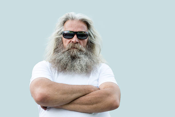 senior man with long hair and beard portrait A portrait of a senior man with long grey hair and a long beard standing in front of a  wall with his arms crossed. He is wearing a white shirt, dark sunglasses  and he is looking straight and serious at the camera. There is some copy space on the right side of the photo. long hair stock pictures, royalty-free photos & images