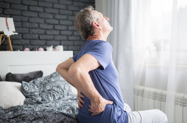 Senior man with lower back pain siting on bed Portrait of senior man with lower back pain siting on bed back pain stock pictures, royalty-free photos & images