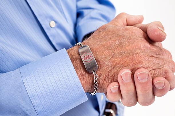 Senior man with medical alert bracelet stock photo